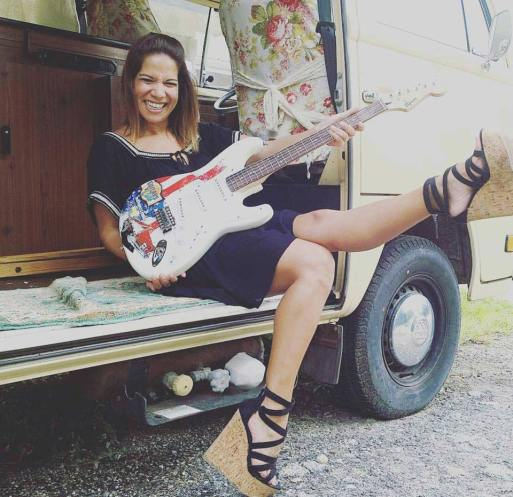 Woman holds real Fender™ promo guitar by AXE HEAVEN®