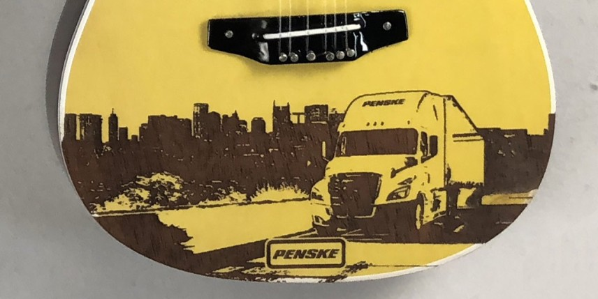 Close-up of Penske Promotional Laser Engraving on Acoustic Mini Guitar by AXE HEAVEN®