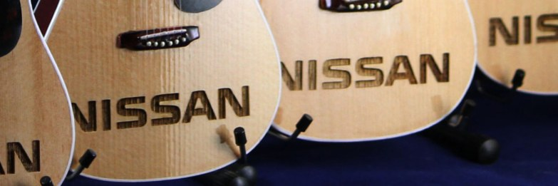 Closeup of Nissan Logo Laser-Engraved into AXE HEAVEN® Acoustic Mini Guitar Promotional Item