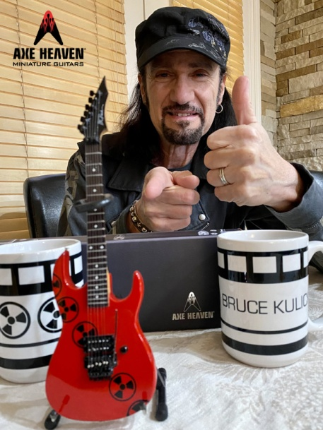 Bruce Kulick Gives a Thumbs-Up to a Bruce Kulick B.C. RICH® Radioactive Mini Guitar Replica Collectible by AXE HEAVEN®
